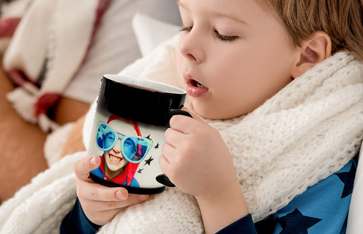 Young boy holding custom designed magic mug with photo of himself on