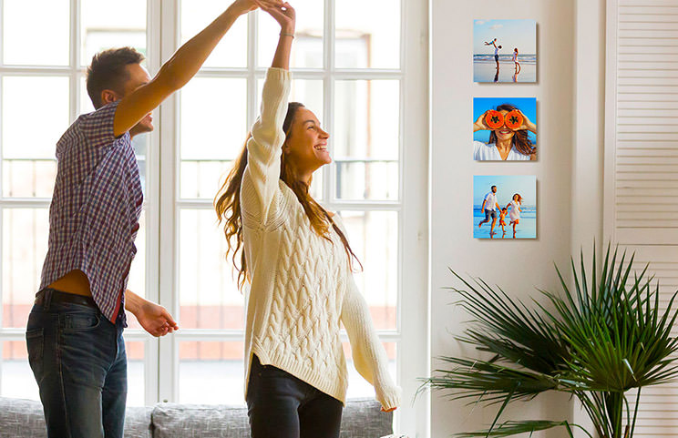 Romantic couple dancing in lounge in front of three custom photo tile prints