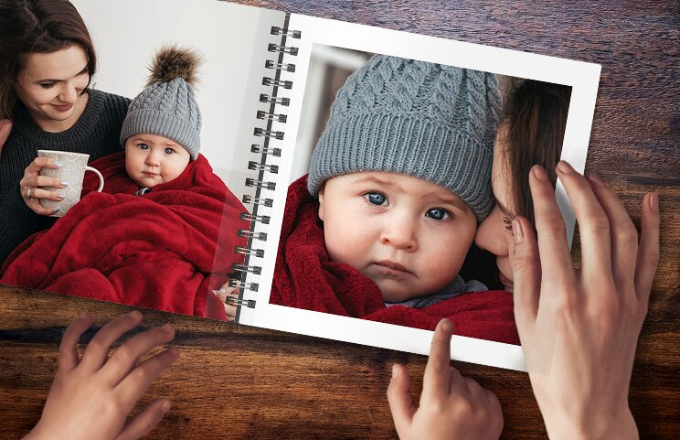 A spiral book open with two photos of a baby
