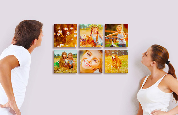 Man and woman looking at six photo tile prints with pictures of kids on