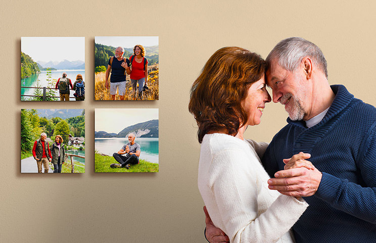 Married couple cuddling in front of four photo prints of them on holiday